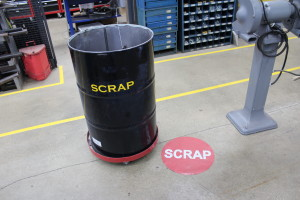 Self adhesive rubber floor sign marks location of scrap bin.