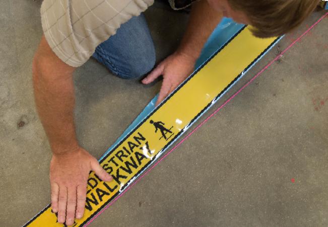 Employee Applying Floor Marking Tape to Warehouse Floor