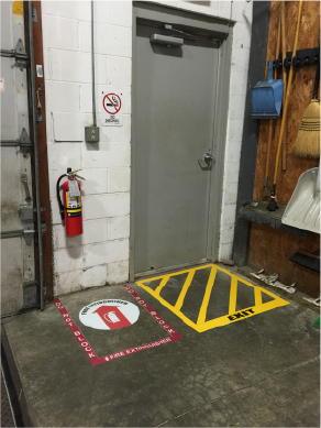 Fire extinguisher and exit locations are marked with floor tape to ensure the areas remain free from clutter
