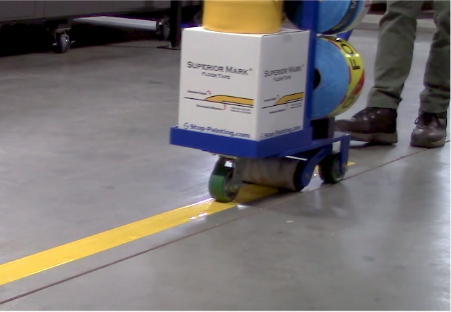 A floor marking tape tamping cart applying a straight yellow line