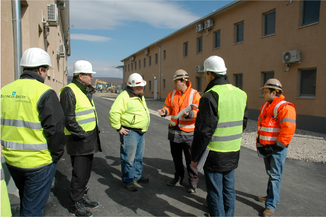 A group of employees wearing safety vests and hard hats discussing worksite safety